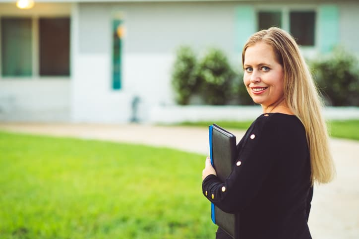 Female property appraiser with file folder stands outside a single family home