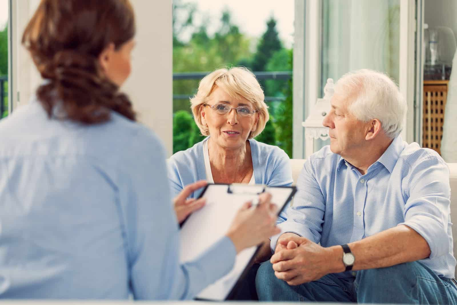 real estate agent talking with elderly couple