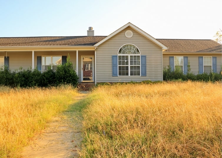 Foreclosed ranch style home with overgrown lawn