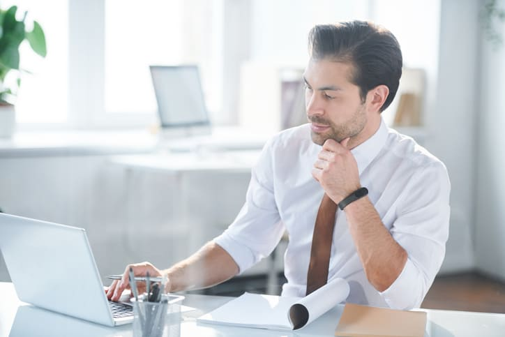 Real estate appraiser working at desk assessing data reliability