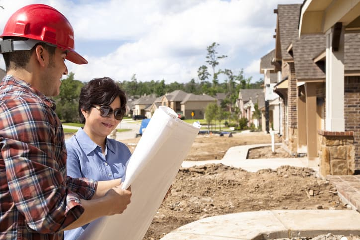 Builder meeting with woman at new home under construction