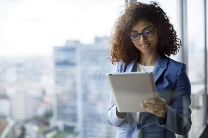 Young smiling businesswoman using using digital tablet in office