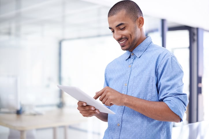 Shot of a young real estate professional using a digital tablet in a modern office