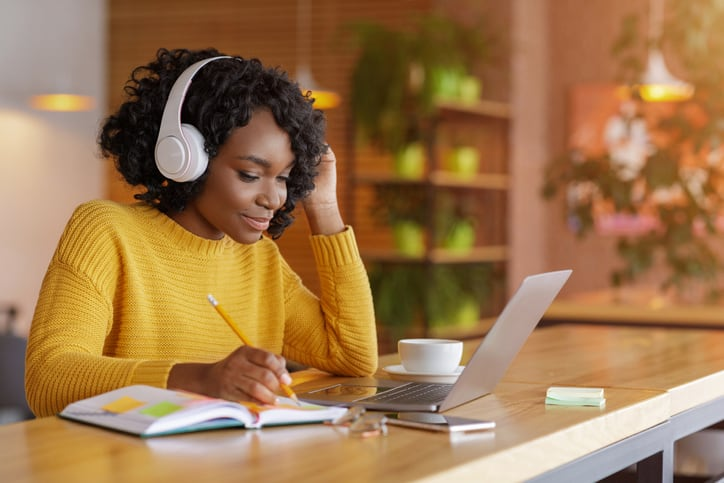 Smiling black girl with wireless headset studying online for the national real estate appraiser exam
